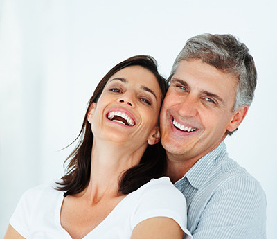 Couple smilng about their new dental implants by their dentist in Pontotoc, MS.