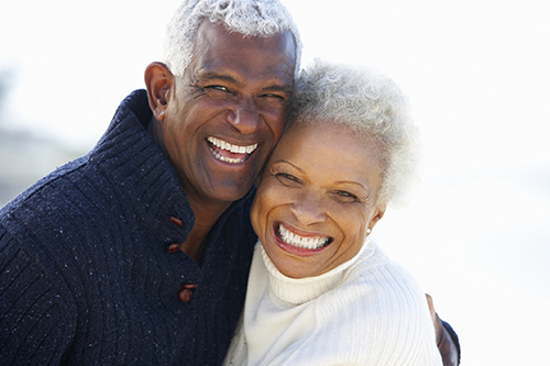 Older couple in Pontotoc, MS smiling about their dental implants.