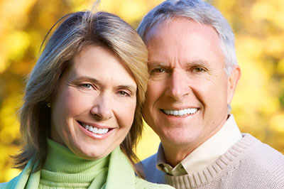 Couple smiling about their new dental implants by their dentist in Pontotoc, MS.